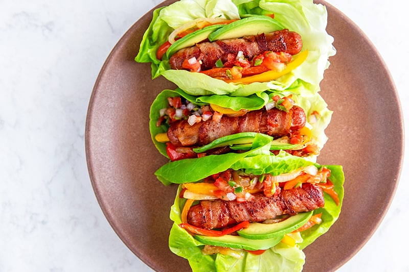 A brown plate with three lettuce-wrapped bacon-wrapped Sonoran hot dogs topped with salsa, sliced avocado, peppers, and onions.