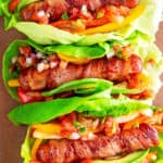 An overhead shot of Whole30, keto, and paleo Sonoran hot dogs wrapped in lettuce and topped with salsa.