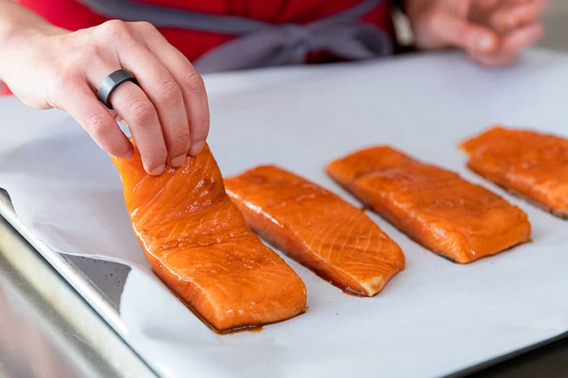 Placing the marinated teriyaki salmon fillets on a parchment lined rimmed baking sheet.