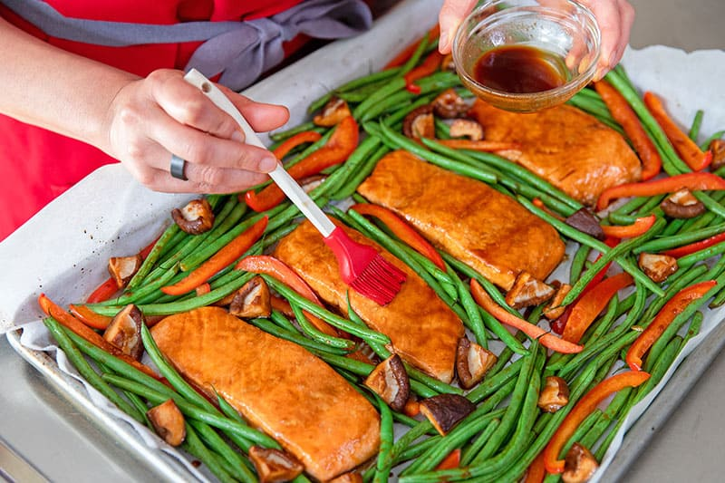 Brushing All-Purpose Stir-Fry Sauce on top of the finished Sheet Pan Teriyaki Salmon.