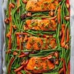 An overhead shot of Whole30 and paleo Teriyaki Salmon Sheet Pan, four cooked salmon fillets surrounded with cooked green beans and bell peppers.