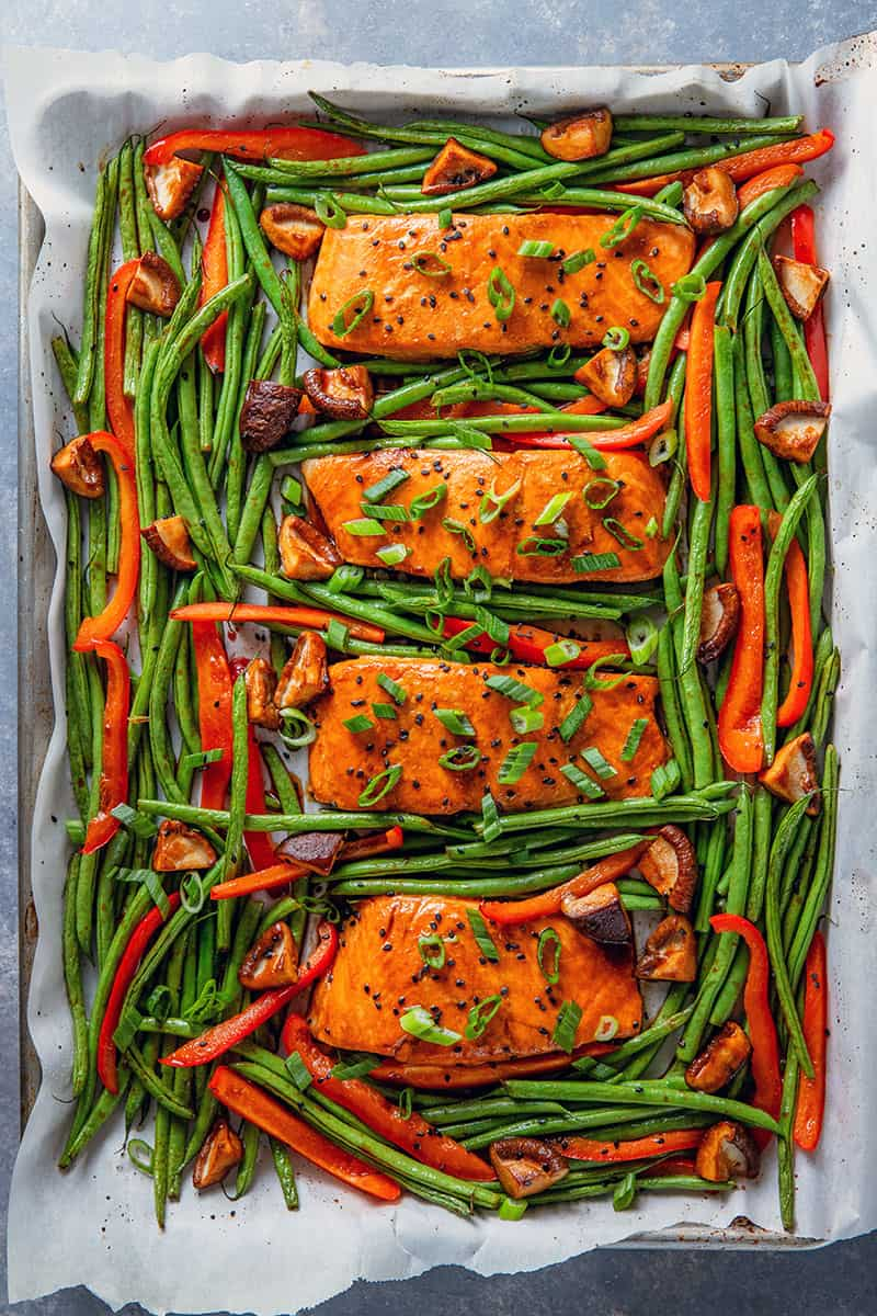 An overhead shot of Whole30 and paleo Teriyaki Salmon Sheet Pan. Four cooked salmon fillets are surrounded with cooked green beans, bell peppers, and shiitake mushrooms and topped with black sesame seeds and scallions.