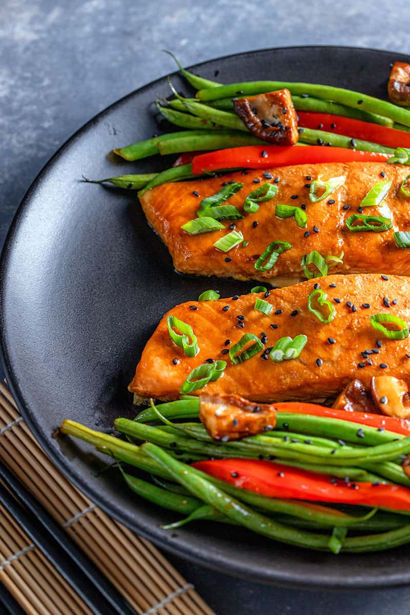 An overhead shot of a black plate topped with two Whole30 Teriyaki salmon fillets and roasted green beans, red bell peppers, and shiitake mushrooms.