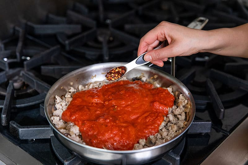 A hand adding spoonful of crushed red peppers to a stainless steel skillet filled with cooked sausage, mushrooms, and marinara sauce.