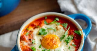 An overhead shot of three blue cocottes filled with Whole30 eggs in purgatory, baked eggs in a spicy tomato meat sauce