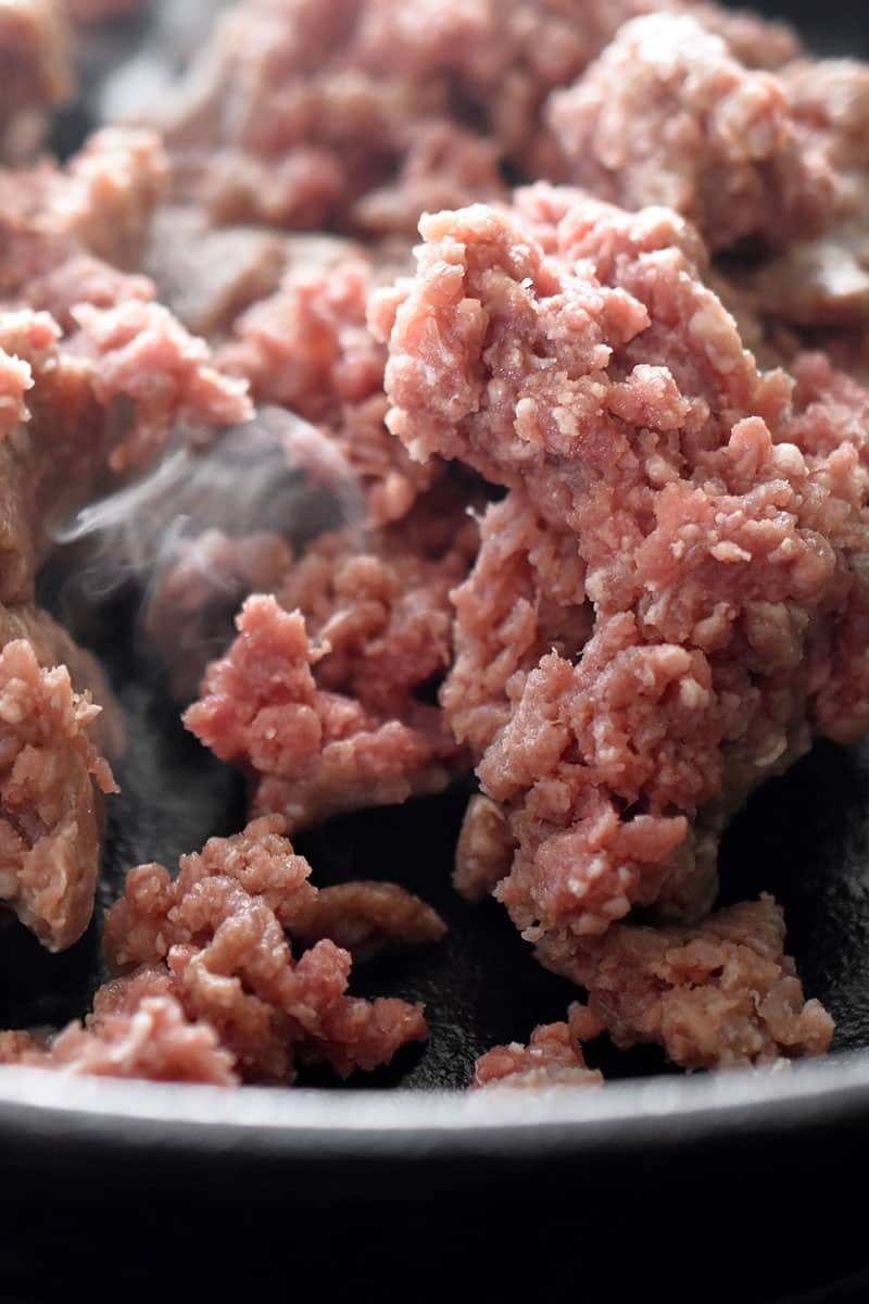 Close up shot of raw ground beef in a skillet to make Tex-Mex Beef and Cauliflower Rice Casserole.
