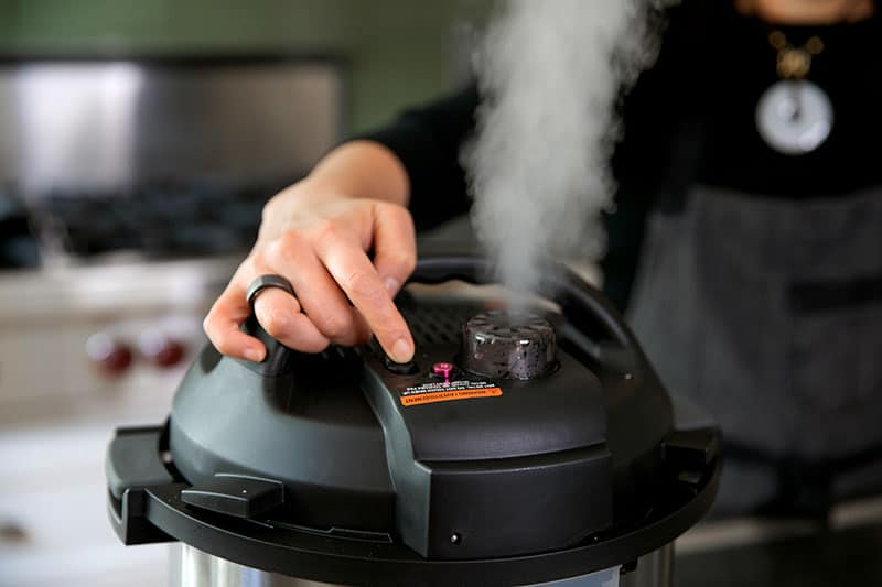 A woman is manually releasing the pressure valve on an Instant Pot and there is steam coming out of the top.