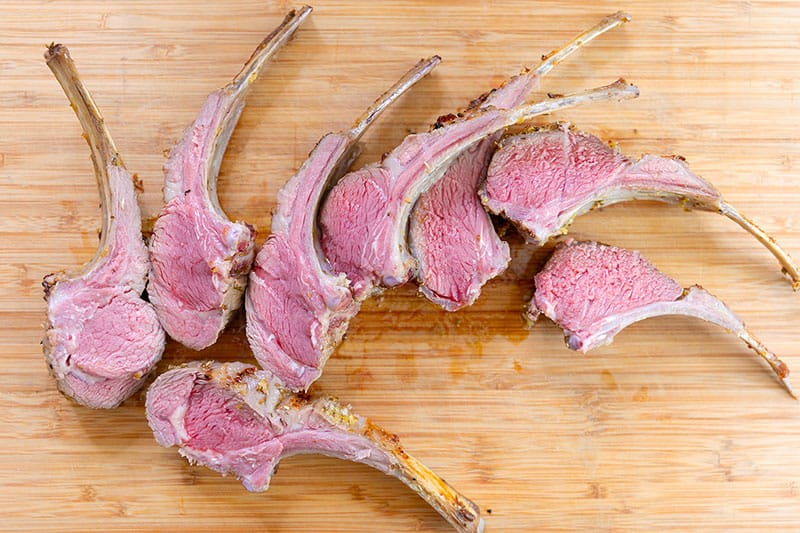 A cutting board topped with lamb chops that are pink, perfectly cooked medium rare.