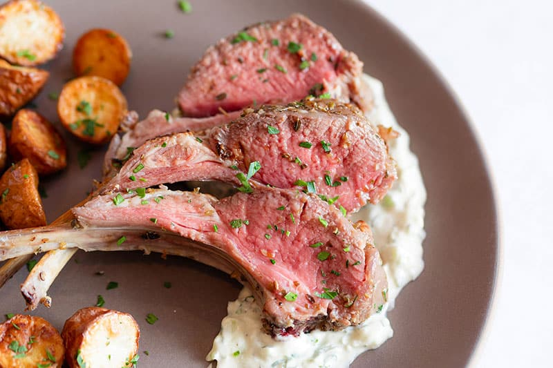 A closeup shot of Whole30 rack of lamb with dairy-free Tzatziki Sauce.