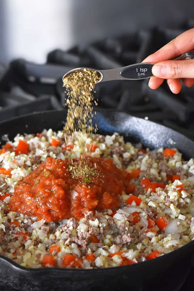 Someone adding a spoonful of oregano to a cast iron skillet filled with ground beef, cauliflower rice, salsa, red peppers and onions.