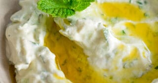 An overhead shot of keto, low carb, paleo, and Whole30 Tzatziki Sauce in a brown bowl topped with olive oil and mint.