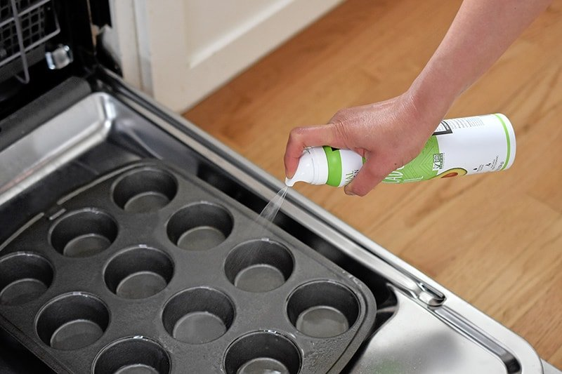 Spraying a muffin pan with avocado oil on an open dishwasher door.