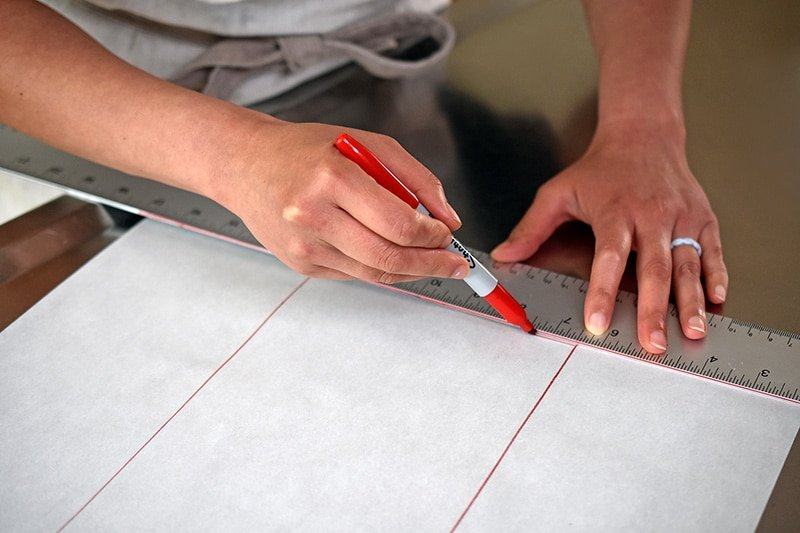 Someone tracing a long rectangle on a piece of parchment paper with a red pen.