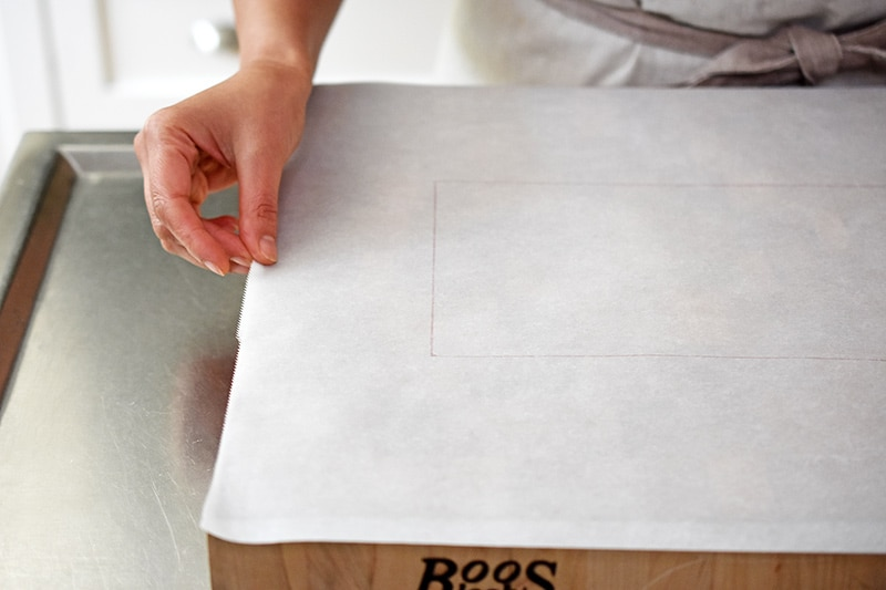 Placing a piece of parchment paper on top of a wooden cutting board. The rectangle is still faintly visible on the paper.