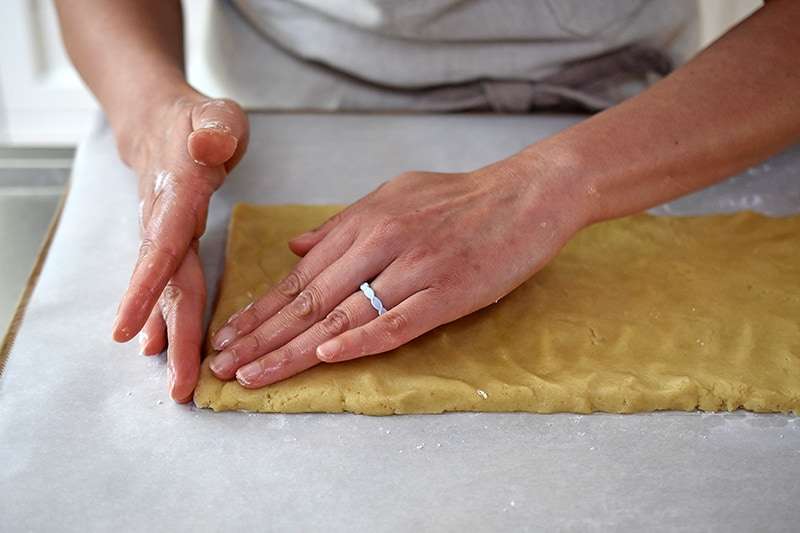 Two hands are shaping the paleo cinnamon roll dough into a thin rectangle shape on top of parchment paper.