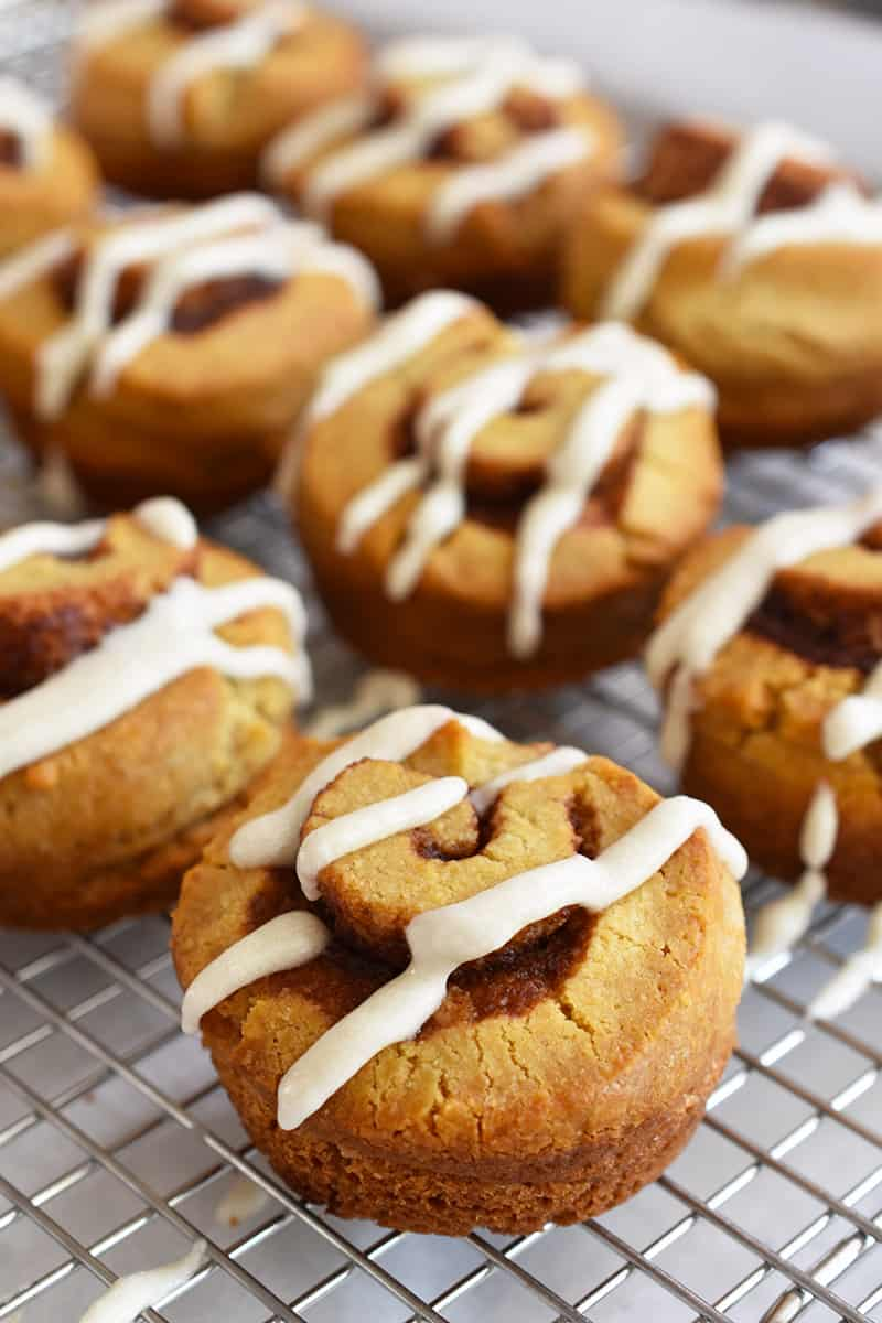 A closeup of a paleo cinnamon roll on a wire rack.