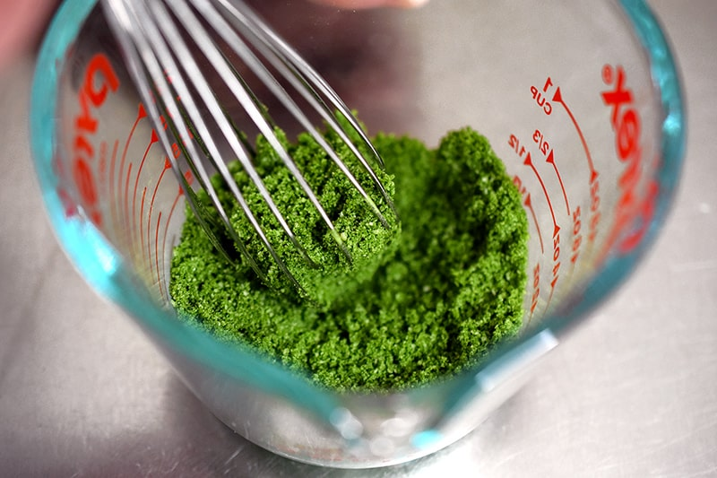 An overhead shot of a whisk combining the dry ingredients of paleo matcha mug cake in a measuring cup.