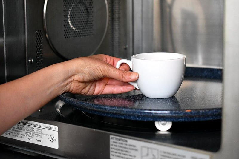 A hand placing a white coffee mug filled with paleo matcha mug cake into an open microwave.