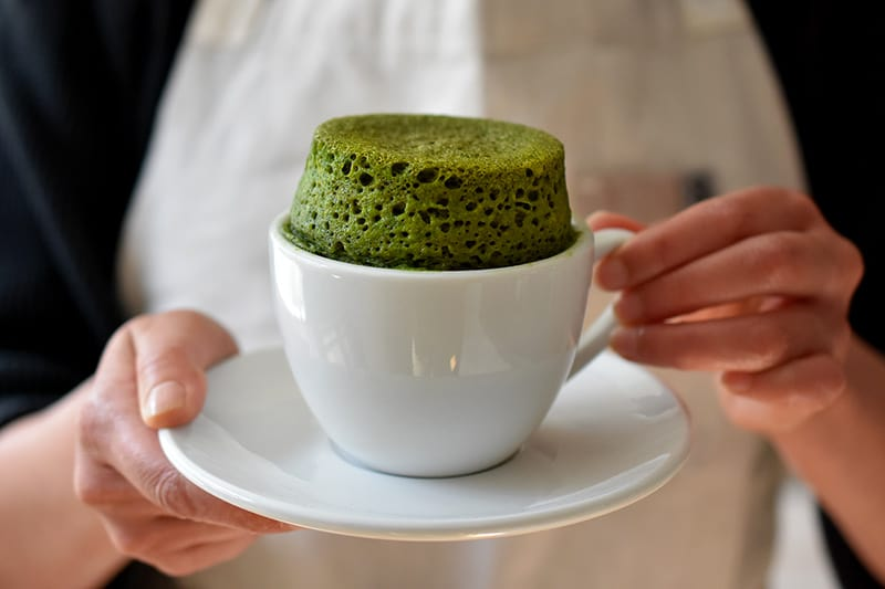 A woman is holding a white coffee mug and saucer. The mug is filled a puffed up green matcha mug cake.