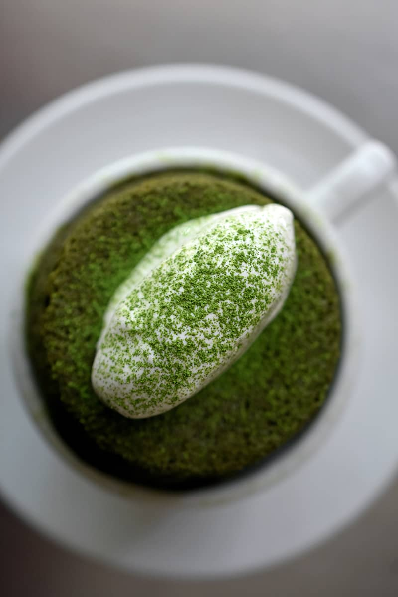 An overhead shot of white coffee mug filled with a gluten-free mug cake topped with coconut whipped cream and dusted with matcha powder.