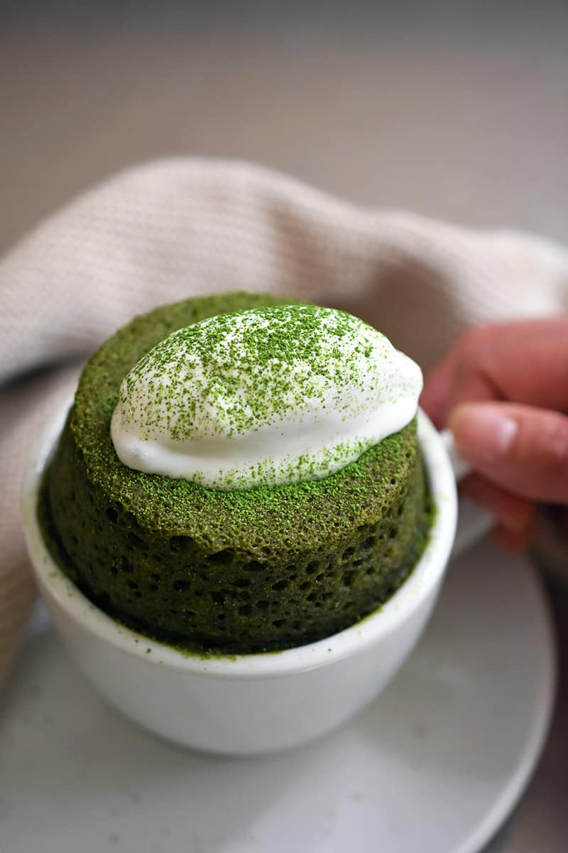A hand holding the handle of a white mug filled with paleo matcha mug cake and topped with dairy-free whipped coconut cream.