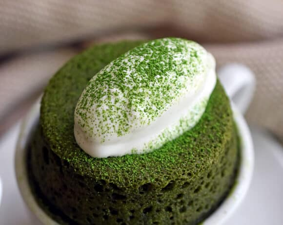 A close-up of a grain-free and gltuen-free matcha mug cake puffed over a white coffee mug and topped with dairy-free coconut whipped cream.
