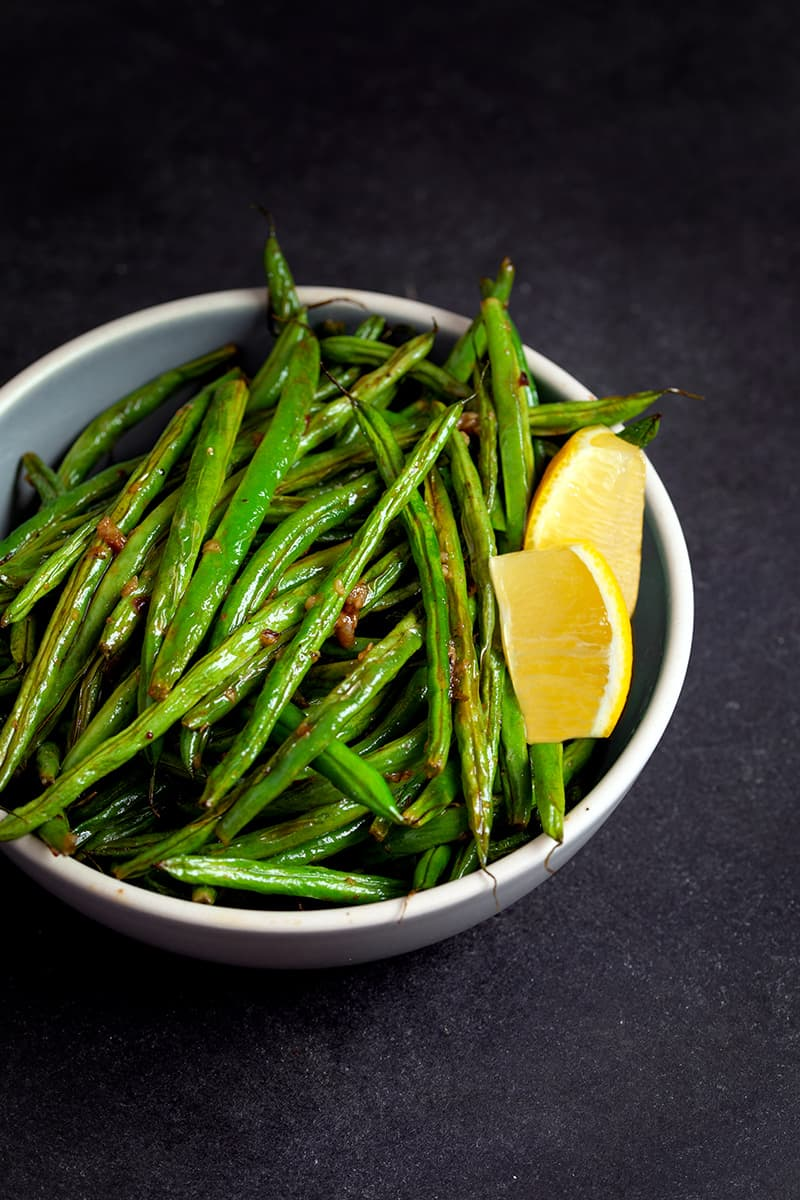 A bowl filled with roasted green beans with lemon and garlic and two lemon slices.