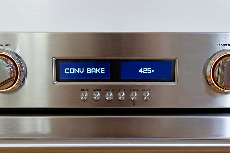 A closeup of an wall oven display that says CONV BAKE 425°F