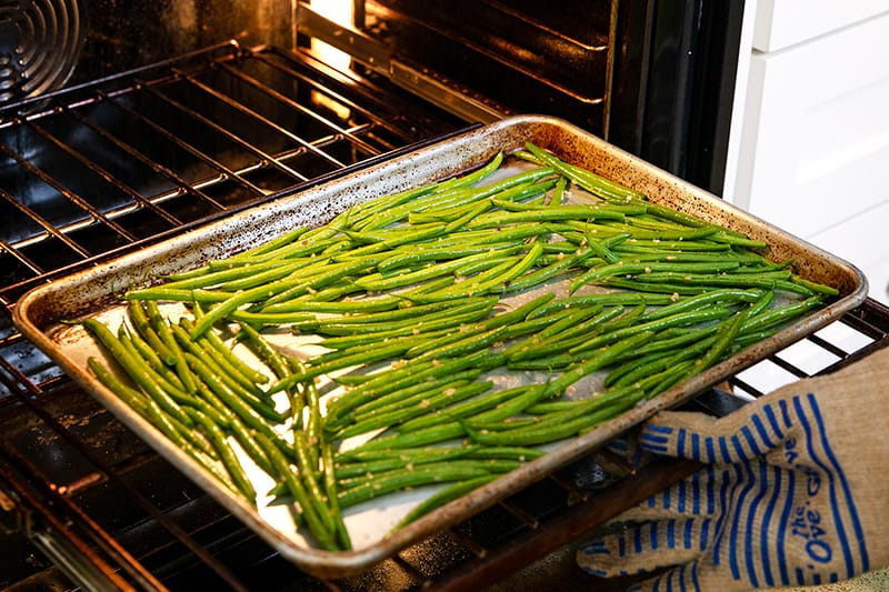 Putting a rimmed baking sheet with green beans into an oven.