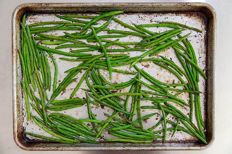 An overhead shot of a rimmed baking sheet with roasted green beans with lemon and garlic.