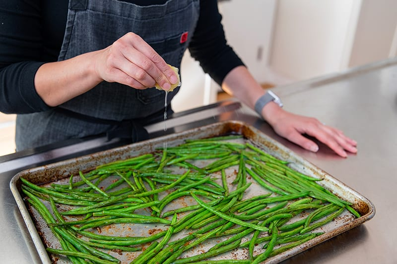 Squeezing a lemon wedge onto a pan of roasted green beans with garlic.