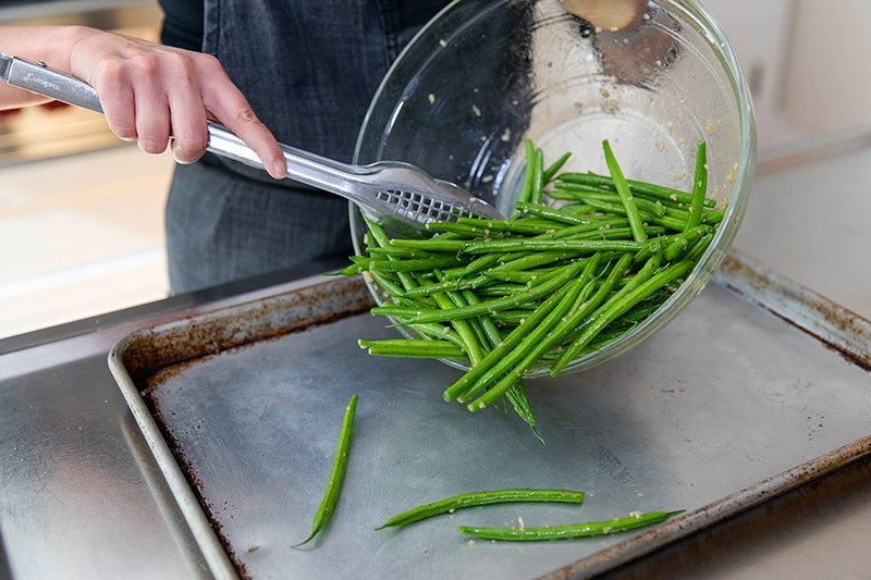 Transferring the marinated green beans to a rimmed baking sheet with a pair of tongs.