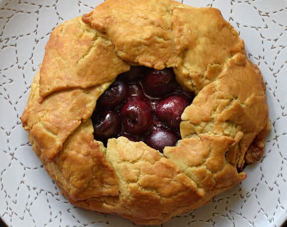 An overhead shot of paleo and gluten-free cherry galette on a white plate