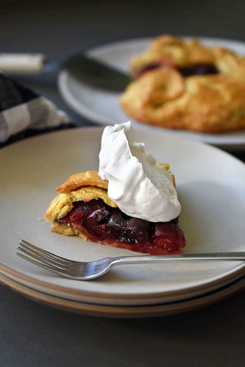 A slice of paleo cherry galette topped with whipped coconut cream is in the foreground of the picture.