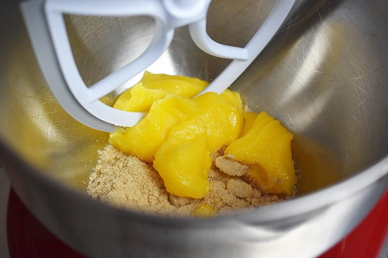 A stand mixer bowl has ghee and maple sugar in it, along with the paddle attachment.