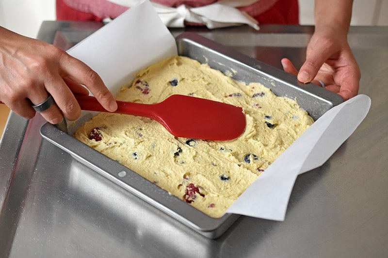 A red silicone spatula is smoothing the top of berry snack cake batter in a parchment lined square metal pan.