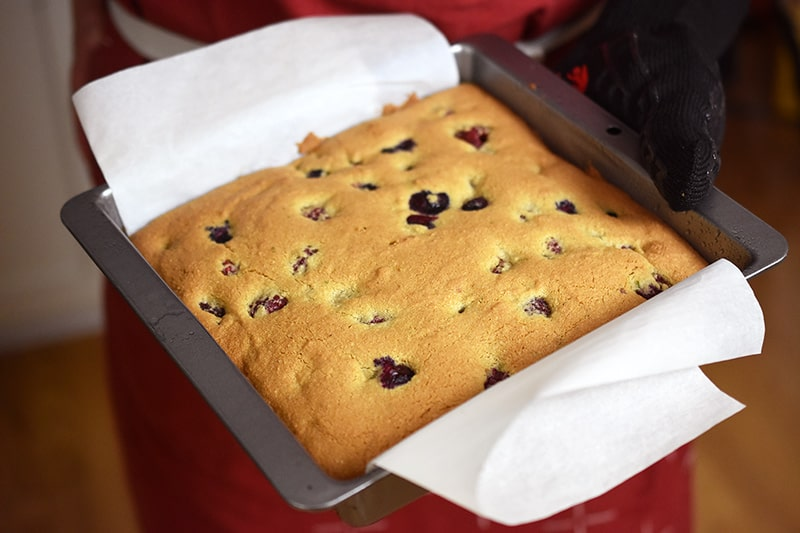 A golden brown berry snack cake is being removed out of the oven.