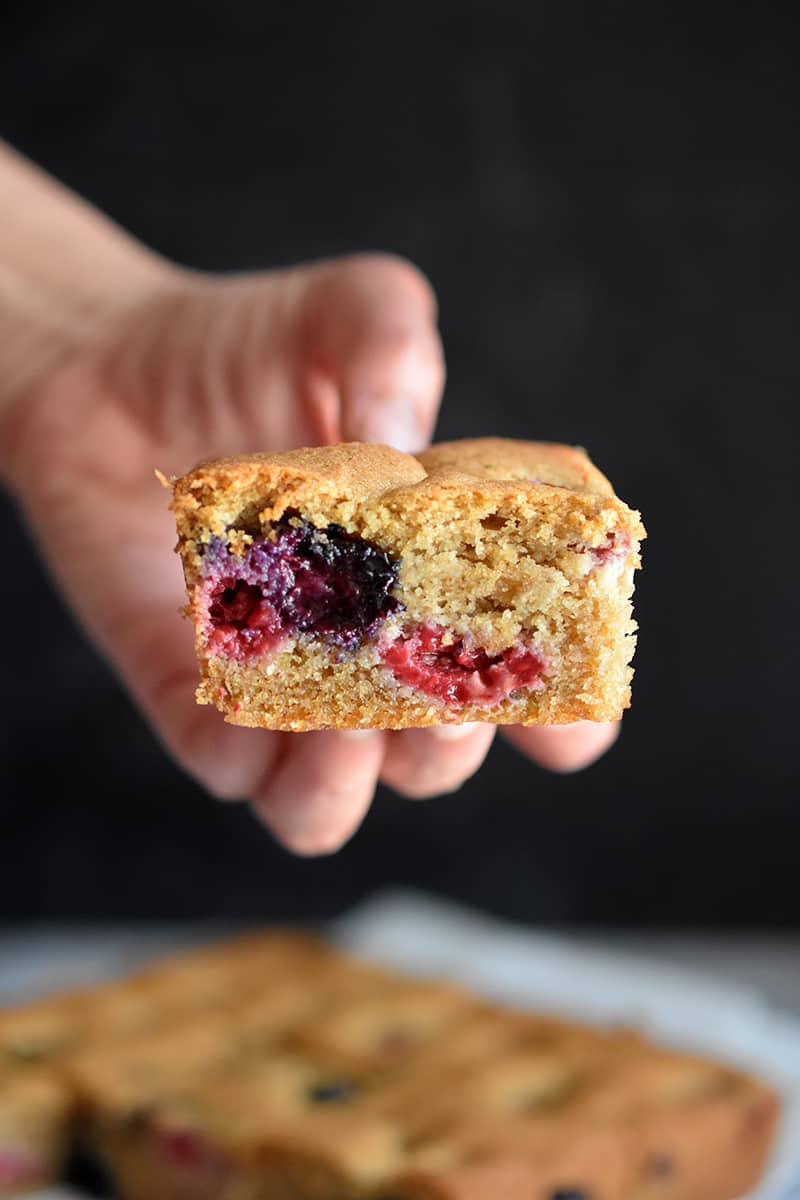 Someone holding a square slice of paleo and gluten-free berry snack cake.