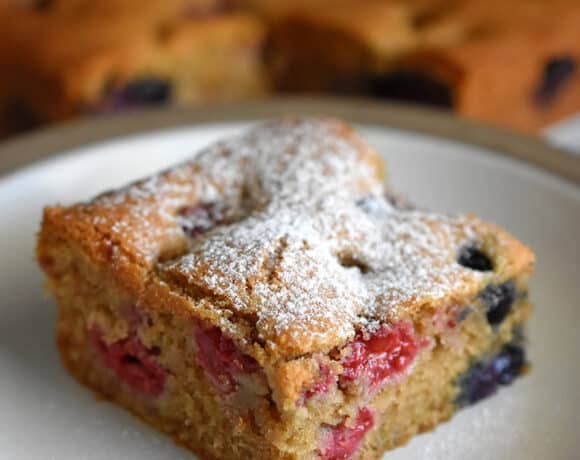 A slice of paleo and gluten-free berry snack cake is on a white plate. In the background are the other slices of berry snack cake.