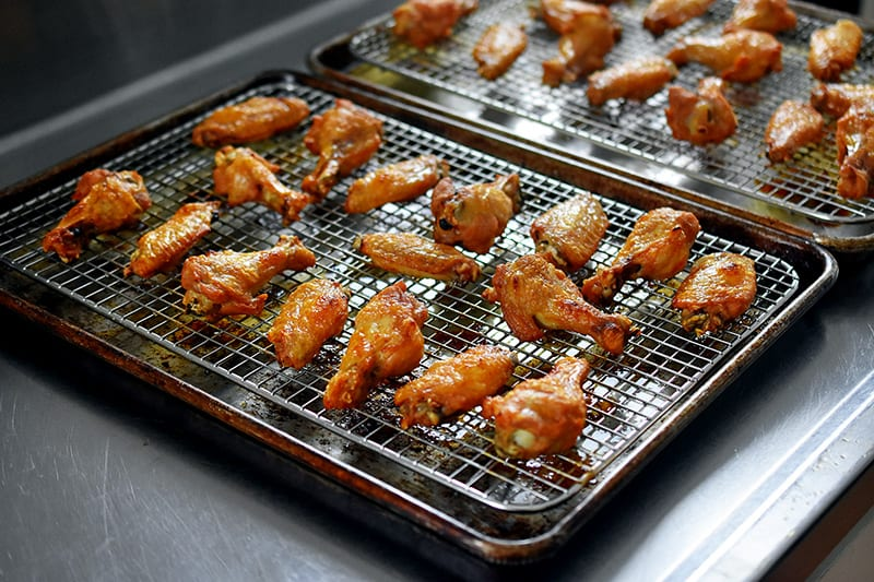 Two trays of golden brown crispy oven baked chicken wings on the counter.