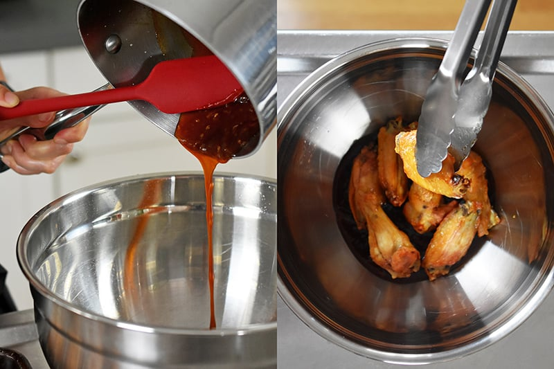 A saucepan is pouring sauce into a metal mixing bowl and adding crispy chicken wings in the bowl.