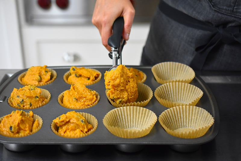 Using a large ice cream scoop to divide the pumpkin chocolate chip muffin batter into the muffin tin.