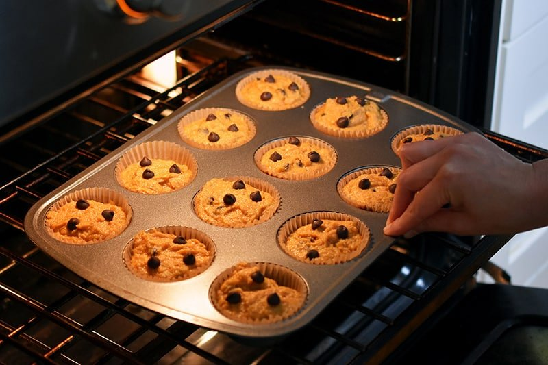 Placing the unbaked paleo pumpkin chocolate chip muffins into the oven.