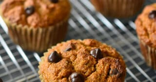 A side angle shot of a dozen paleo and gluten free pumpkin chocolate chip muffins cooling on a wire rack.