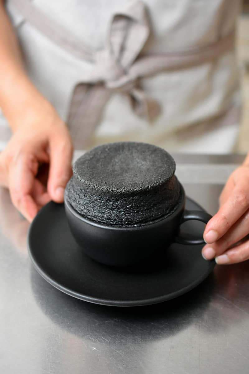Two hand holding a black tea cup filled with a puffed up gluten free and paleo black sesame mug cake.
