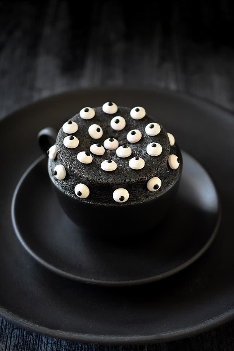 A black mug on a two black plates is filled with a black sesame cake topped with candy eyeballs.