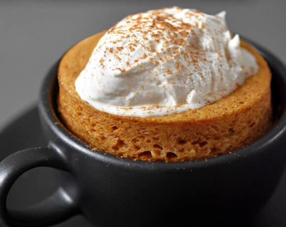 A black coffee mug filled with paleo and gluten-free pumpkin mug cake cooked in the microwave.The cake is topped with whipped coconut cream and dusted with pumpkin spice blend.