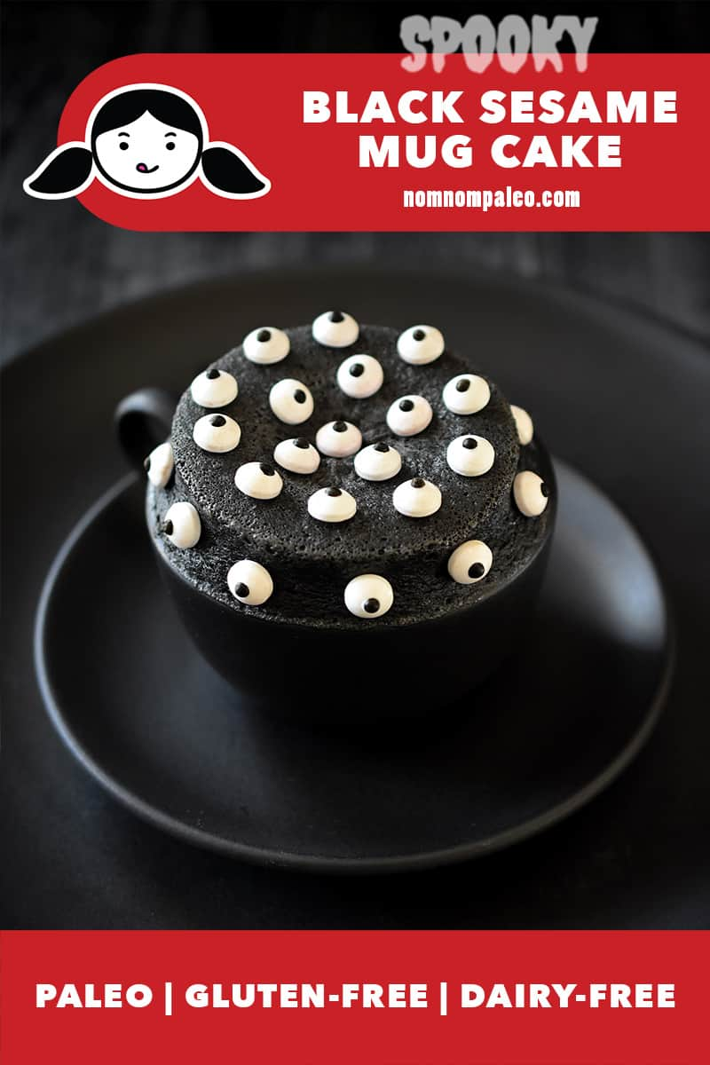 A closeup of a black sesame mug cake in a black mug on a two black plates. The black cake is covered with candy eyeballs. The red banner on the bottom says it is paleo, gluten free, and dairy-free.