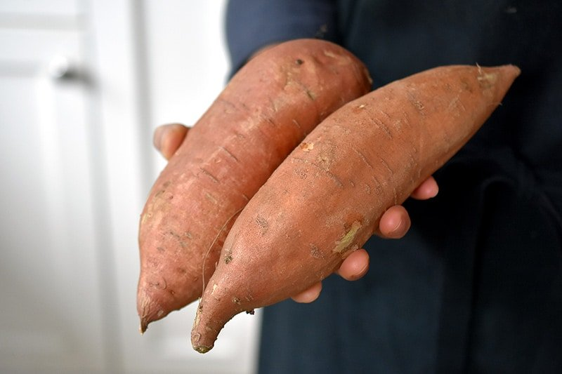 A hand holding two unpeeled garnet sweet potatoes.
