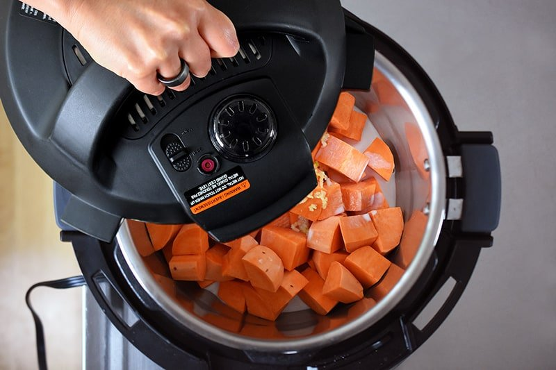 Putting the lid on an Instant Pot to cook mashed sweet potatoes.